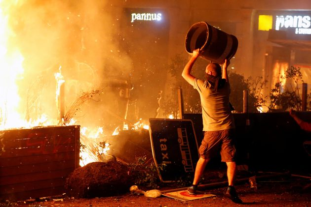 Un manifestante radical lanza una papelera al
