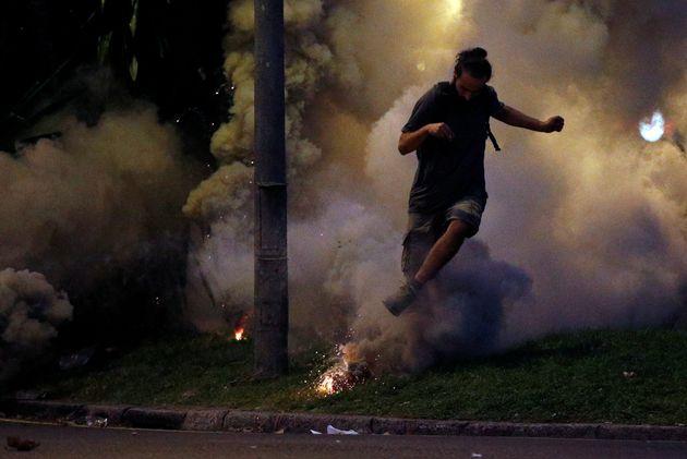 Un manifestante huye por el humo de un