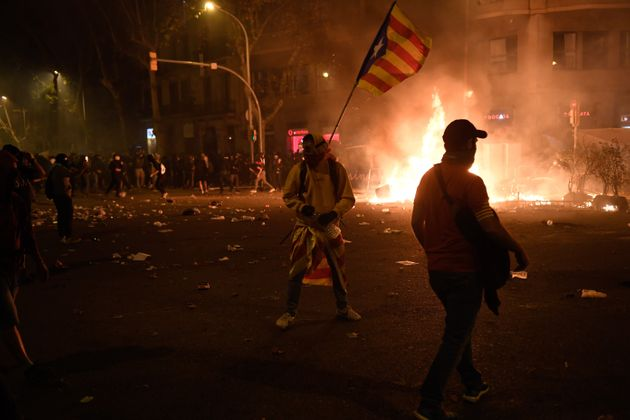 BARCELONA, SPAIN - OCTOBER 18: Protesters throw objects during clashes near the Police headquarters in...