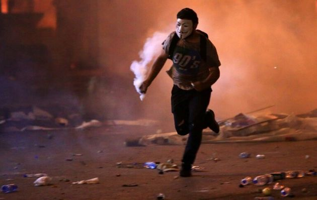 Un manifestant masqué court avec une grenade lacrymogène lors de heurts avec les forces de sécurité,...