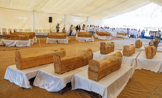 Archaeologists stand around painted ancient coffins at Al-Asasif necropolis, unveiled by Egyptian antiquities...