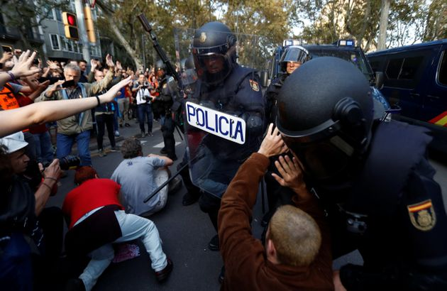 Riot police try to remove Catalan demonstrators during a protest in central Barcelona, Spain, October...
