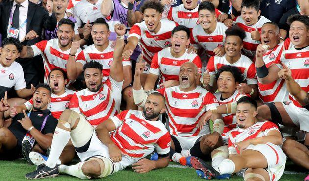 1次リーグ・日本-スコットランド。決勝トーナメント進出を決め、記念撮影する日本代表ら=13日、横浜国際総合競技場