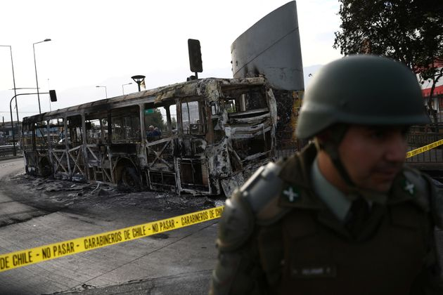 A burned bus is pictured after a protest against the increase in subway ticket prices in Santiago, Chile,...