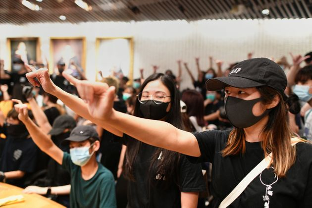 Student protesters gesture in a meeting room after forcing their way into the administrative offices...