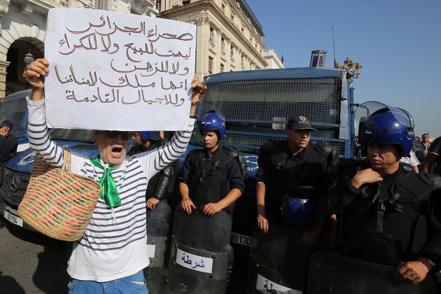 Algerian protesters face riot police at a demonstration near the parliament building in Algiers on October...