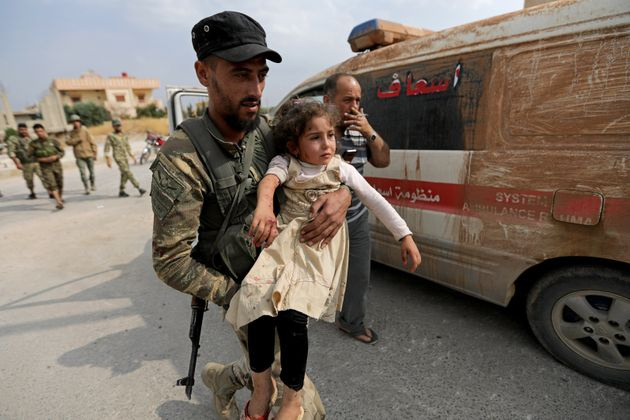 A wounded girl is carried by a Turkey-backed Syrian rebel fighter in the town of Tal Abyad, Syria, on