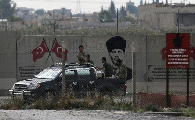 Turkey-backed Syrian rebel fighters return from the Syrian border town of Tal Abyad, as they are pictured...
