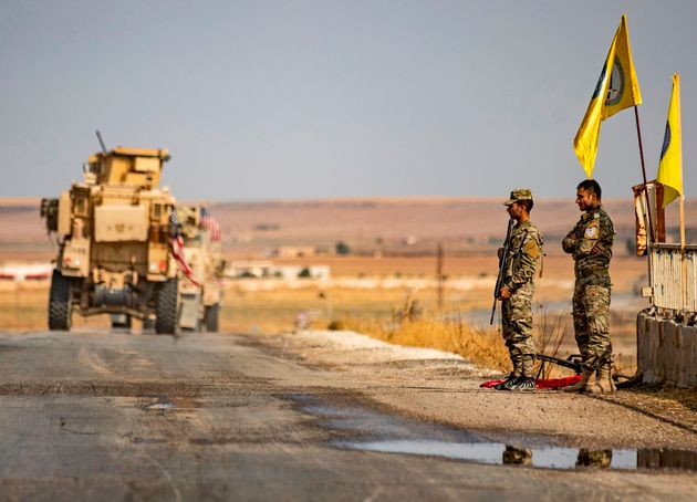 US military vehicles drive on a street in the town of Tal Tamr on Sunday after pulling out of their