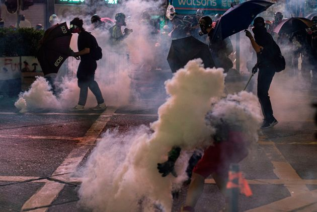 Masked protesters use umbrellas as Hong Kong police fire tear gas during a pro-democracy rally in Kowloon...