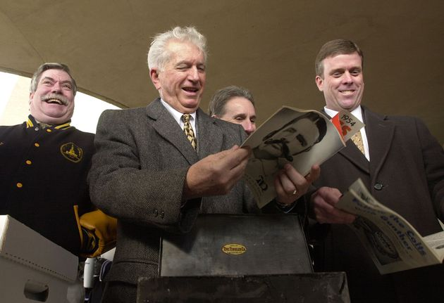 Former Baltimore Mayor Thomas D'Alesandro III (center) and others laugh as they look over the contents...