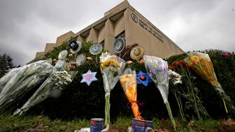 FILE - In this Nov. 20, 2018, file photo, a makeshift memorial of flowers rests on bushes outside the Tree of Life Synagogue in Pittsburgh. A Pittsburgh hospital says Daniel Leger, a chaplain shot during the Tree of Life synagogue mass shooting, has been discharged from the hospital Tuesday, Nov. 27. (AP Photo/Gene J. Puskar, File)