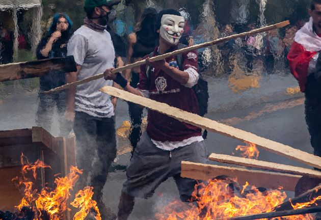 지난 19일 산티아고에서 불 타는 바리케이드에 막대를 집어넣고 있는 시위대. 지난 18일 지하철 요금 인상에 항의하며 지하철역으로 몰려든 고등학생들에 의해 촉발된 이번 시위는 당일...