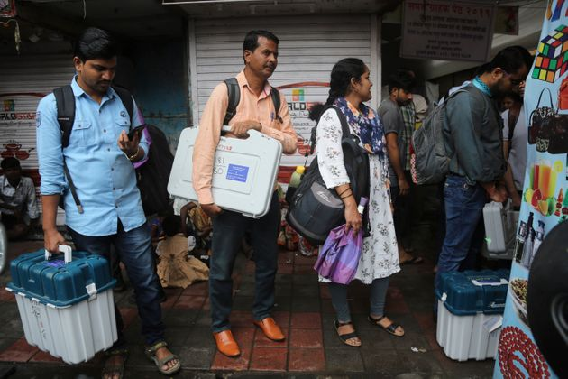 Polling officials hold electronic voting machines and other polling material in Mumbai, Oct 20,