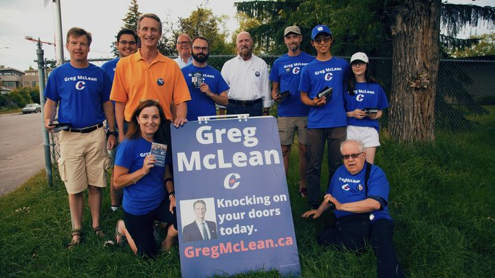 Conservative candidate Greg McLean, in orange shirt, with his wife Ruth, kneeling on the left, pose for a photo with campaign volunteers in  July 2019.