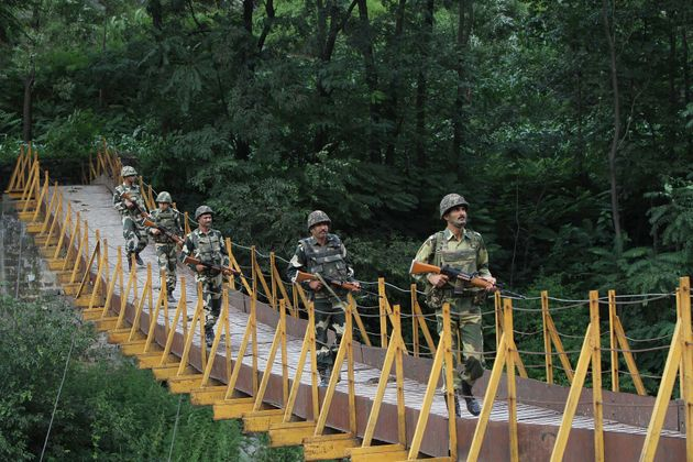 Indian BSF soldiers patrol over a footbridge near the Line of Control (LoC) at Sabjiyan sector of Poonch...