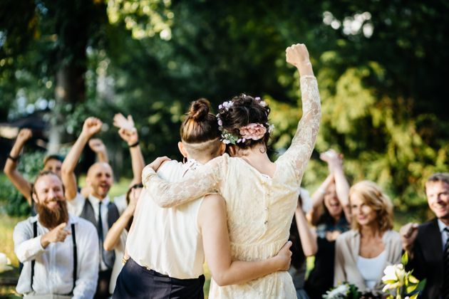 Young lesbian couple celebrating their marriage in front of their friends. The wedding ceremony is