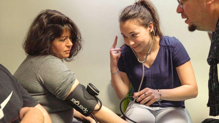 聴診器で血管の音を聴き、血圧を測ろうとする学生。なかなか音が聞き取れず、苦労する