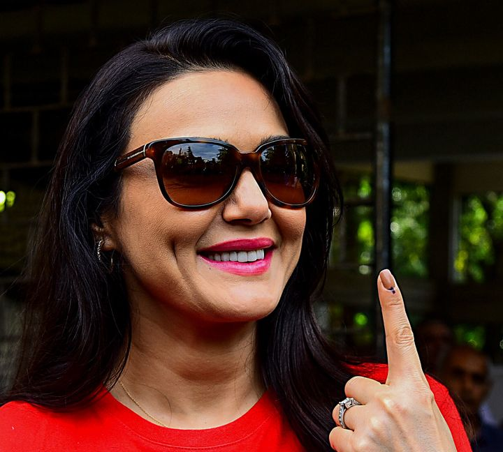 Bollywood actress Preity Zinta shows her inked finger after casting her vote at a polling station.