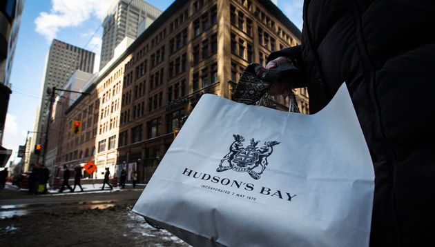 A woman holds a Hudson's Bay shopping bag in front of the Hudson's Bay Company (HBC) flagship department...