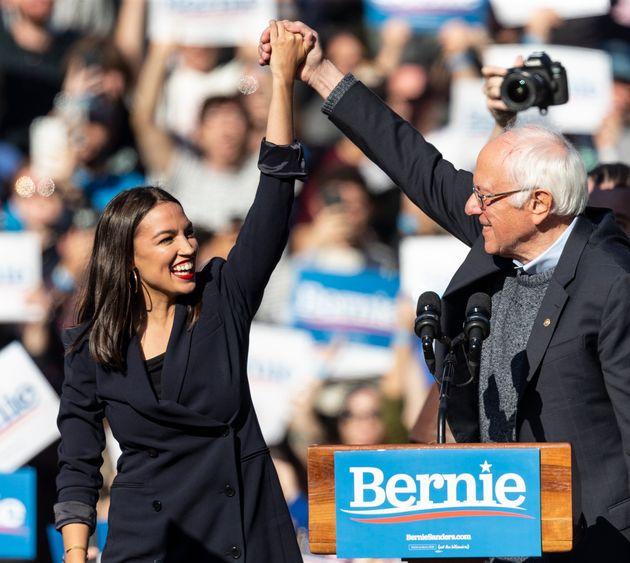Democratic presidential candidate Sen. Bernie Sanders (I-Vt.) joins hands with Rep. Alexandria Ocasio-Cortez...