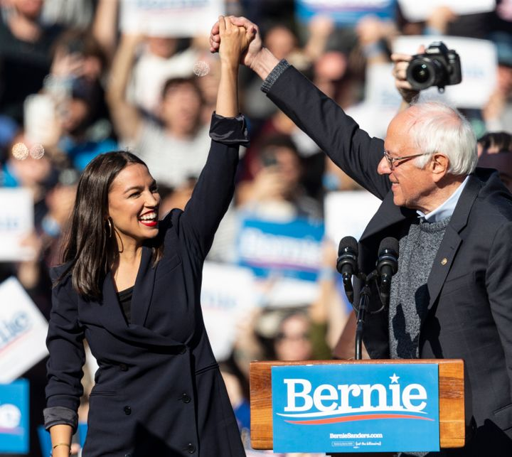 Democratic presidential candidate Sen. Bernie Sanders (I-Vt.) joins hands with Rep. Alexandria Ocasio-Cortez (D-N.Y.) during a campaign rally on Saturday in New York.