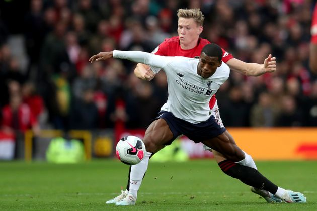 Liverpool's Georginio Wijnaldum, right, fights for the ball with Manchester United's Scott McTominay...