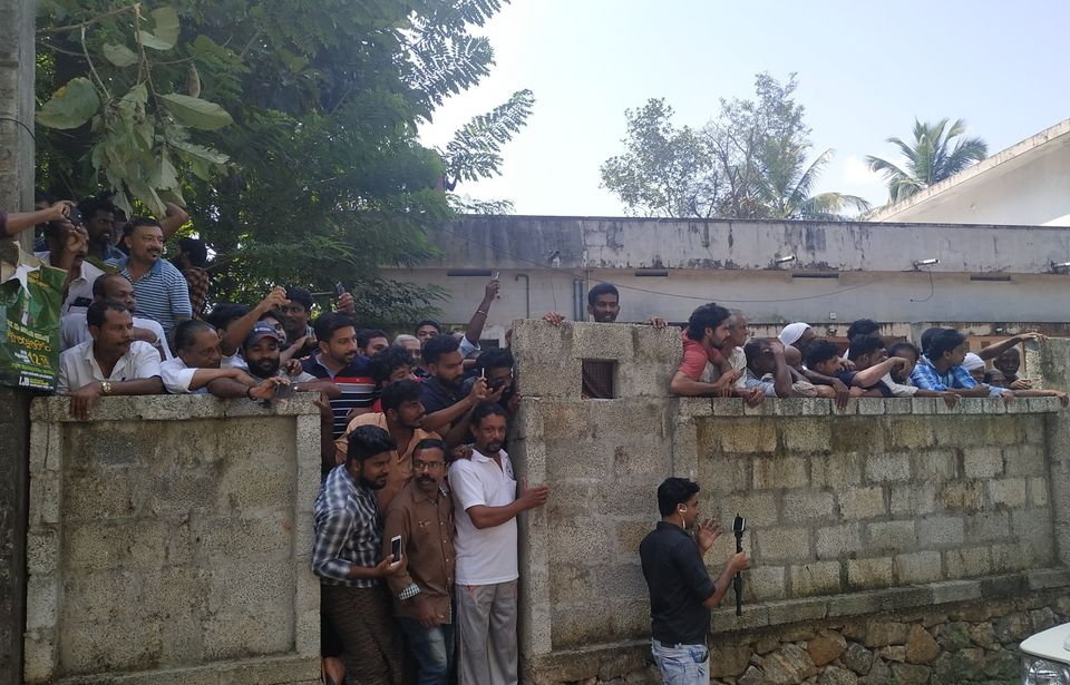 People watch Jolly being brought to the Koodathayi house during the police's
