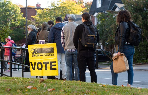 People line up to enter a polling station on election day of the 2019 federal election, in Ottawa on...