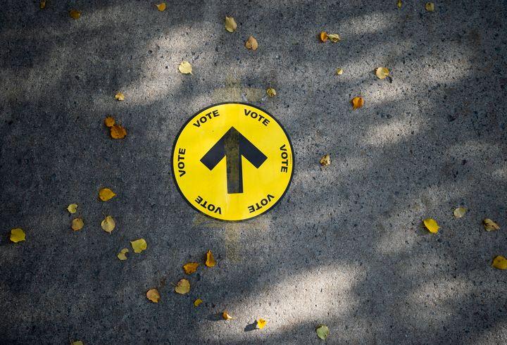 Un panneau indiquant aux électeurs un bureau de vote est collé sur le trottoir parmi les feuilles d'automne, le jour de l'élection fédérale de 2019, à Ottawa (Ontario), le lundi 21 octobre 2019.