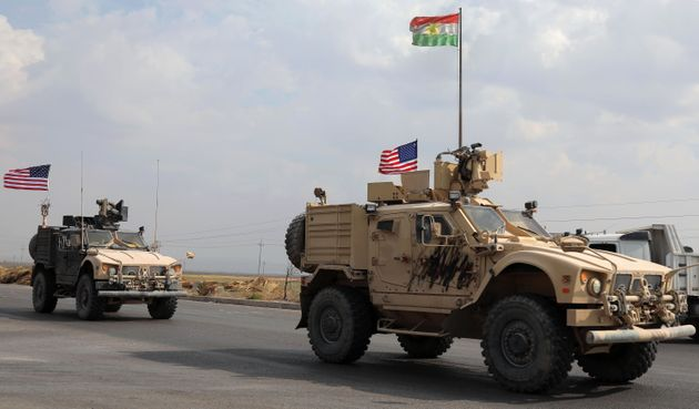 A convoy of U.S. military vehicles arrives near the Iraqi Kurdish town of Bardarash after withdrawing...