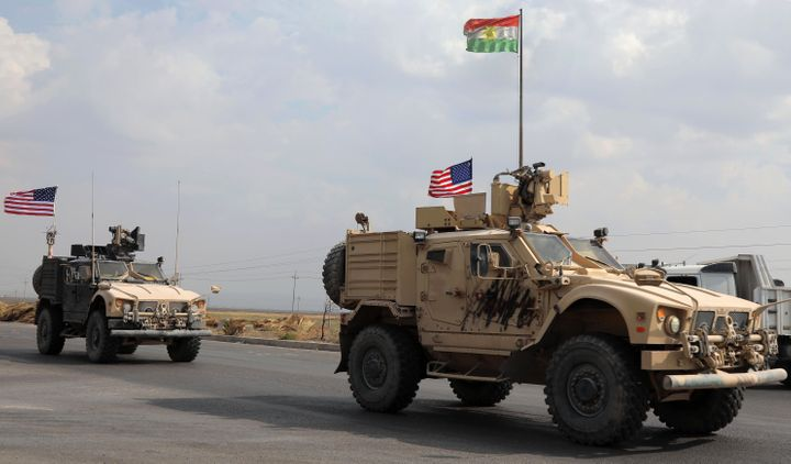 A convoy of U.S. military vehicles arrives near the Iraqi Kurdish town of Bardarash after withdrawing from northern Syria on