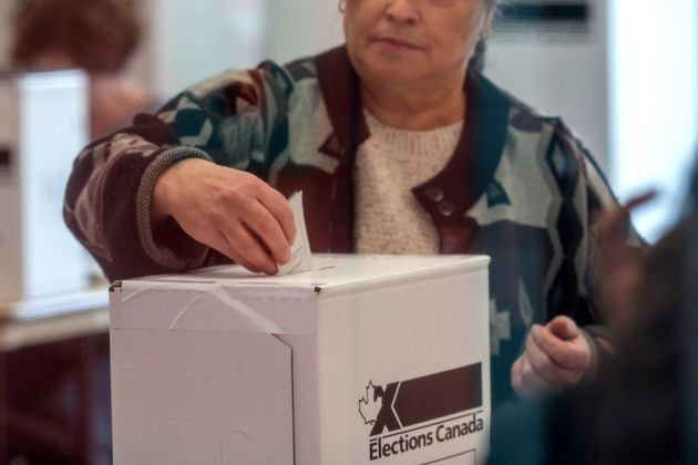 A woman votes at a polling station in Toronto for the federal election, Oct. 21,