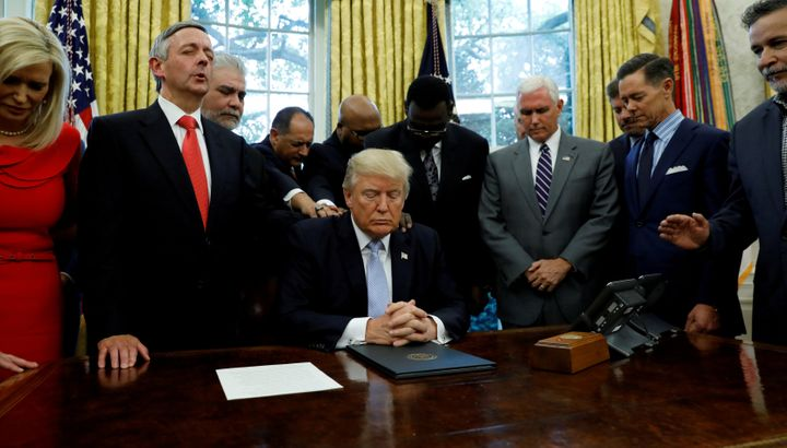 Faith leaders place their hands on the shoulders of President Donald Trump as he takes part in a prayer for those affected by
