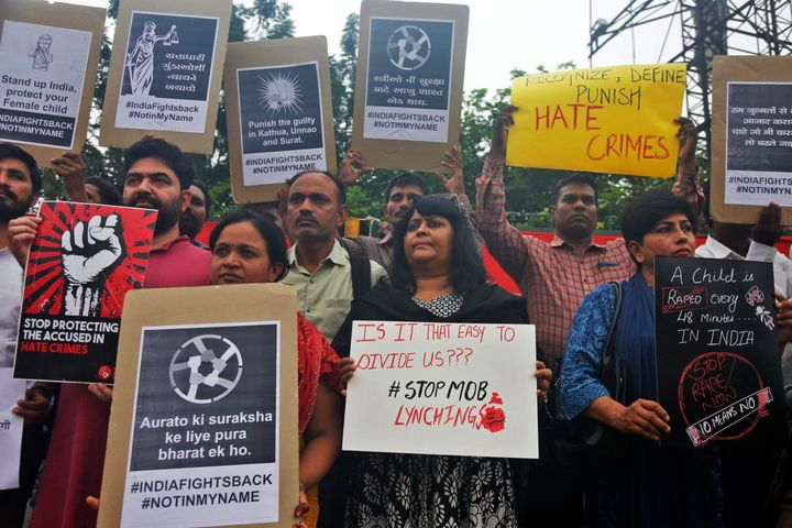 Indians hold placards and shout slogans during a protest against mob attacks in Ahmedabad, July 23, 2018.