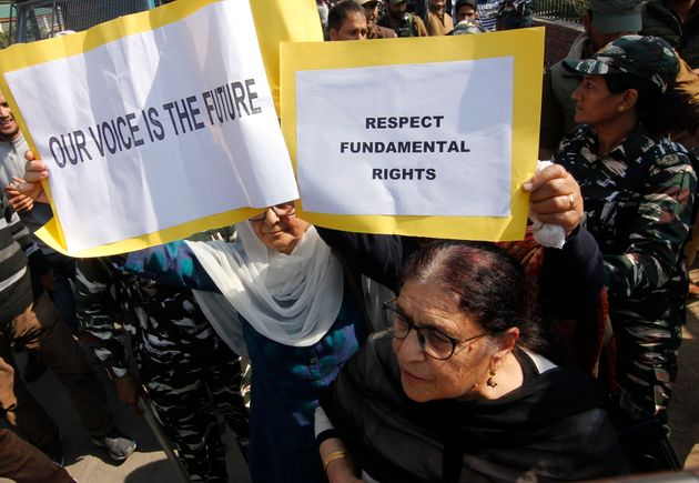 Members of 'Women of Kashmir' a civil society group hold placards as they protest against the revocation...