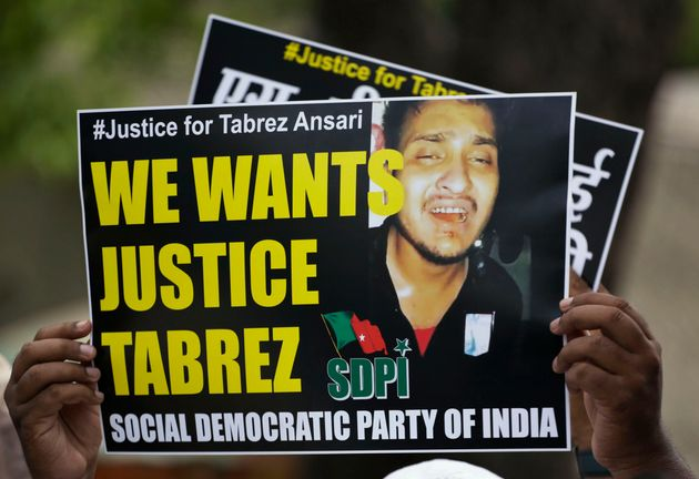 An Indian man holds a placard condemning the mob lynching of Muslim youth Tabrez Ansari in