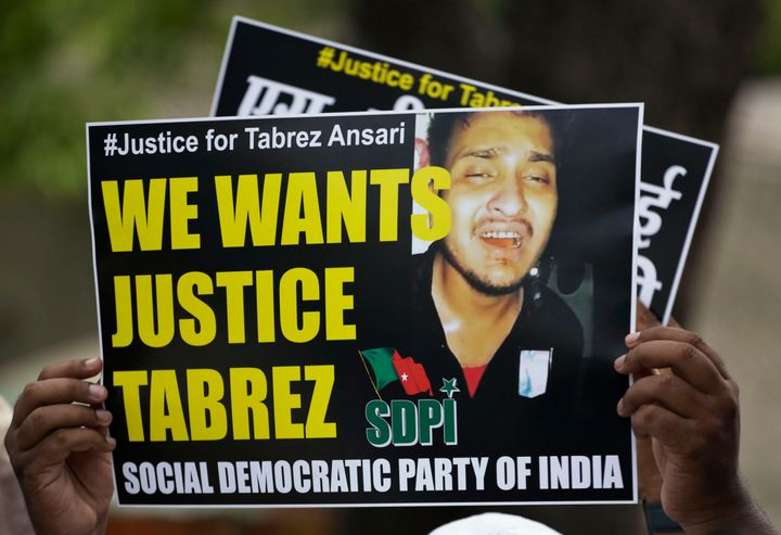 An Indian man holds a placard condemning the mob lynching of Muslim youth Tabrez Ansari in Jharkhand.