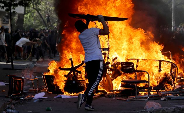 An anti-government protester adds an object to burning chairs and benches amid a march by students and...