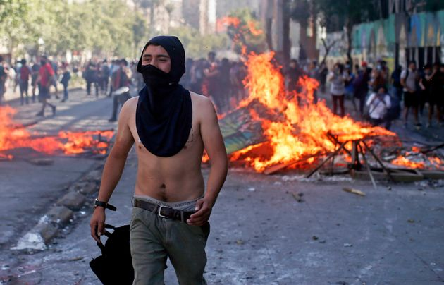 A masked protester walks near a burning barricade during clashes with police in Santiago, Chile, Monday,...