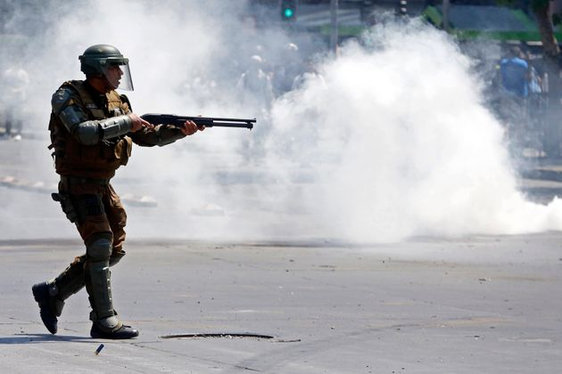 A police officer fires rubber pellets at protesters as a state of emergency remains in effect in Santiago,...