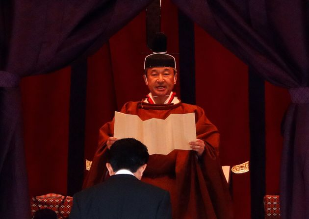 Emperor Naruhito speaks near Japan's Prime Minister Shinzo Abe during a ceremony to proclaim his enthronement...