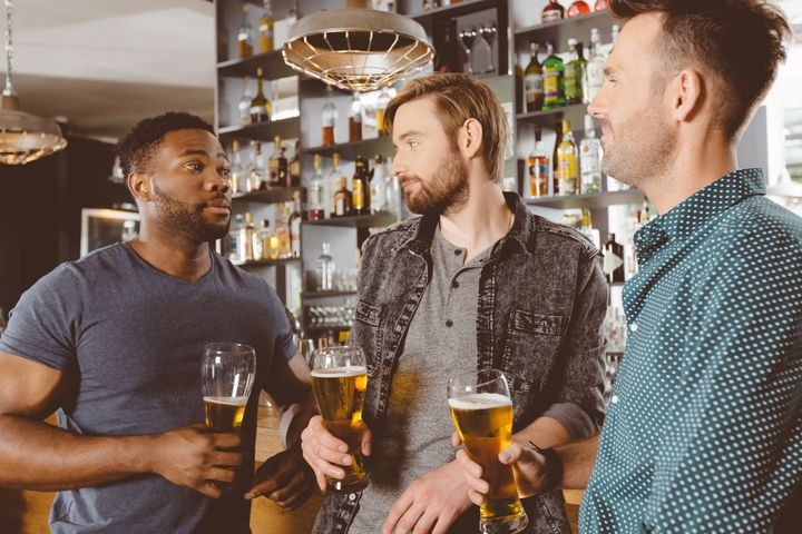 Three multi ethnic friends - caucasian and afro american - meeting in a pub, drinking beer and talking. Bar counter behind them.