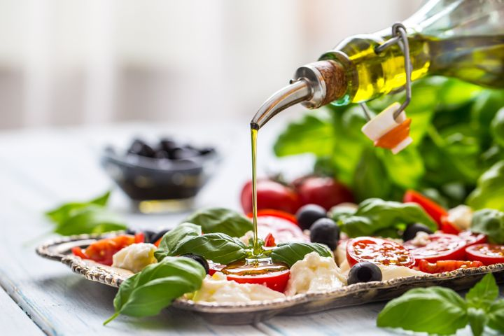 Pouring olive oil on caprese salad. Healthy italian or mediterranean meal.