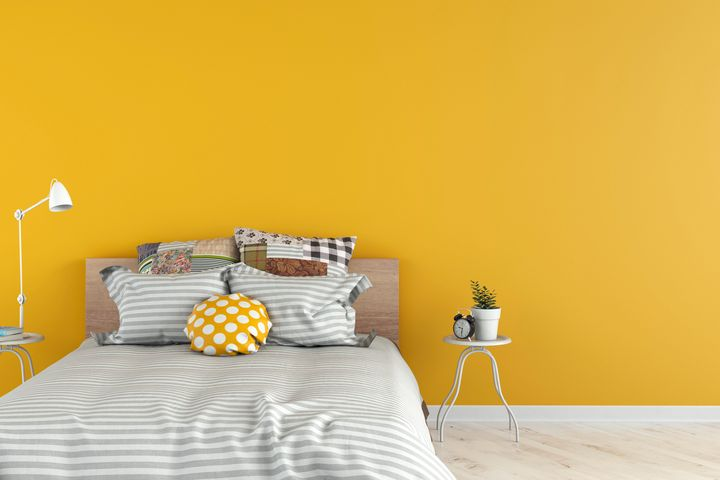 Bedroom with decoration on white hardwood floor in front of empty yellow wall with copy space. 3D rendered image.