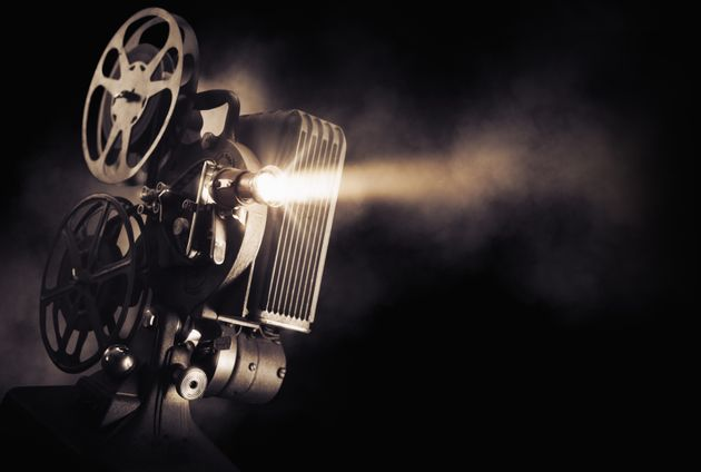 Movie projector on a dark background with light beam / high contrast
