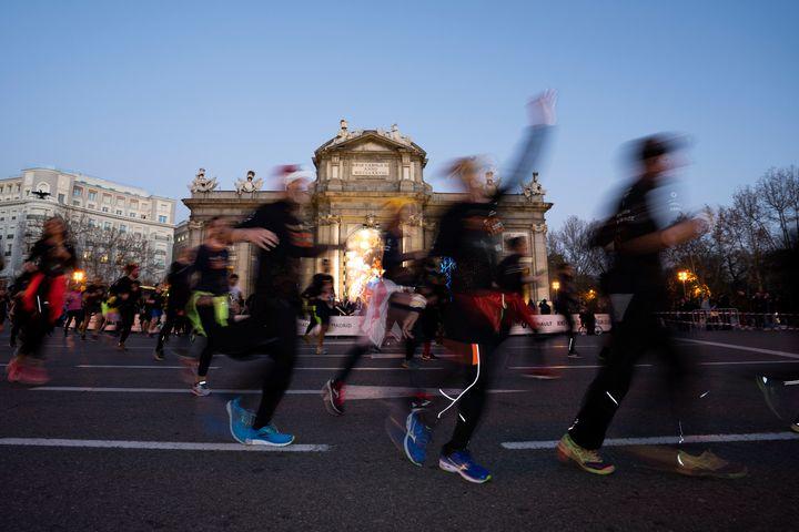 Corredores de la San Silvestre vallecana a su paso por la Puerta de Alcalá en Madrid.