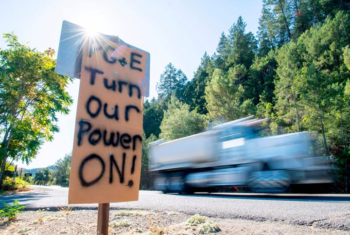 A sign calling for PG&E to turn the power back on is seen on the side of the road during a statewide blackout in Calistog