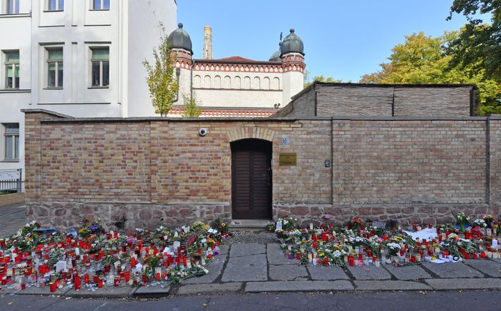 Flowers and candles are placed next to the door of the Halle synagogue, days after a right-wing extremist attack on the congr