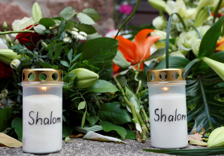 Flowers and candles are seen outside the synagogue in Halle, Germany, October 10, 2019, after two people were killed in a sho